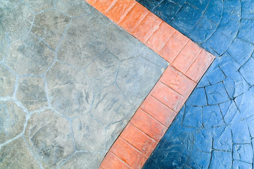 blue stamped concrete and gray stencilled concrete with orange stencilled concrete edgework dividing the two colours and finishes