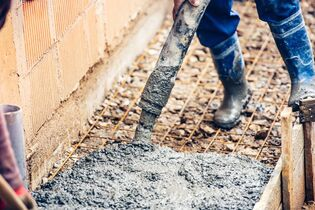contractor pouring concrete slab for footpath