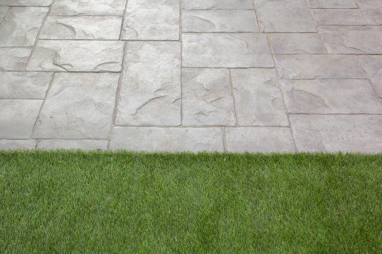 grey stencilled concrete with grass along the edge